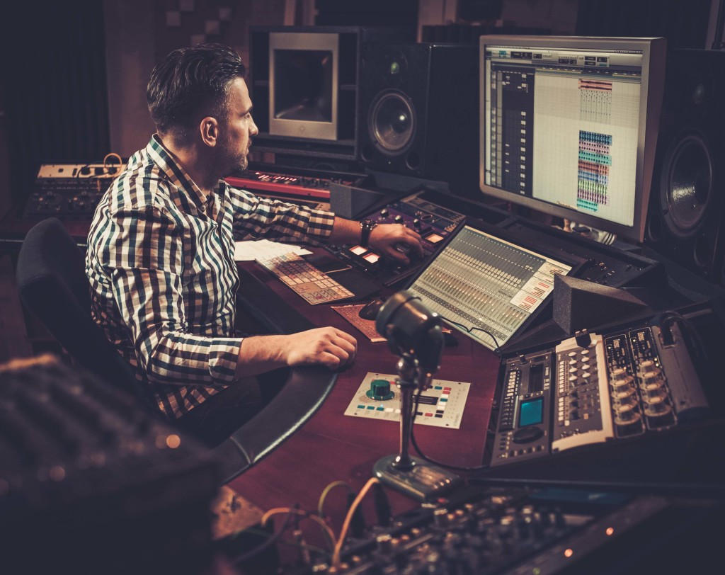 Sound engineer working at mixing panel in the boutique recording studio.; Shutterstock ID 373495885